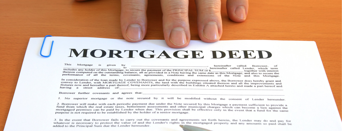 hand touching a document titled Mortgage Deed